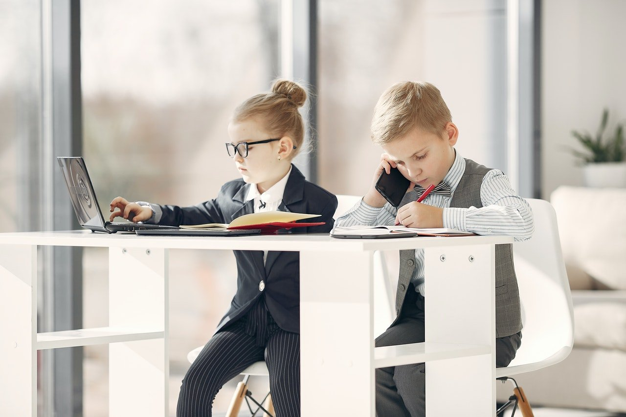 concentrated-business-kids-working-on-laptop-and-smartphone-3874172